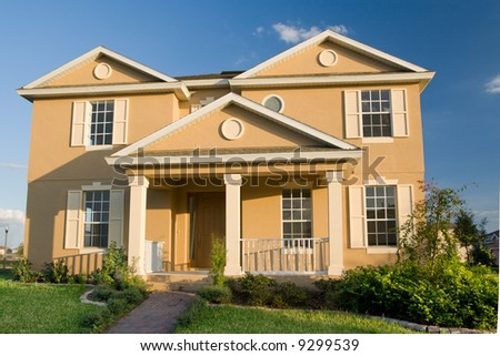 two-story stucco home with landscaped lawn