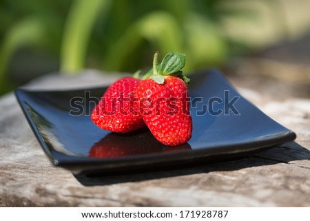 Two strawberries on a black plate outdoors #171928787