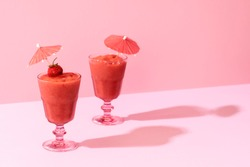 Two strawberry smoothie in a glass with cocktail umbrella on a pink background, in harsh light. Summer tasty mocktails. Healthy dietary drink.