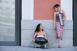 Two street musicians looking each other and laughing, playing instruments.