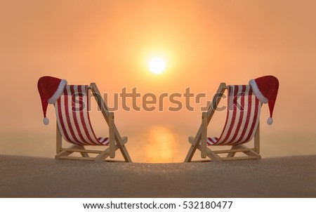 Two striped red-white deckchairs with red Santa hats for romantic couple at ocean sandy beach during sunset. Happy New Year and Merry Christmas travel destinations to hot countries concept