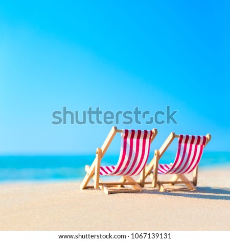 Two striped red-white sunbeds at sandy tropical ocean beach in hot sunny day. Natural travel background. Tourist relaxation concept. #1067139131
