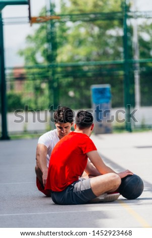 Two strong caucasian athletes resting on the ground at the basketball court while having a conversation. #1452923468
