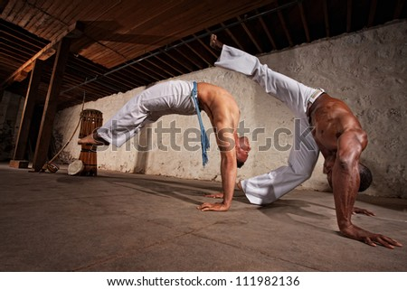 Two strong male capoeira experts fighting indoors