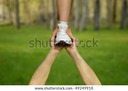 Two strong male hands holding one female foot. Teamwork, support, competition concept