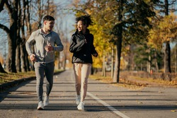 two strong trainers are running in the Park: a woman and a man of African appearance. sports couple friends are actively engaged in fitness aerobics in the morning. healthy lifestyle.