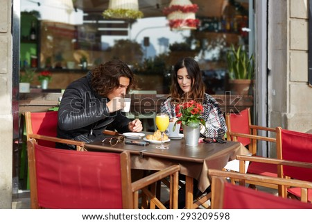 Two student friends drinking cafe after university classes in a restaurant terrace outdoors at cold spring day while they enjoying warm tea and a delicious cake, young couple breakfast in coffee shop