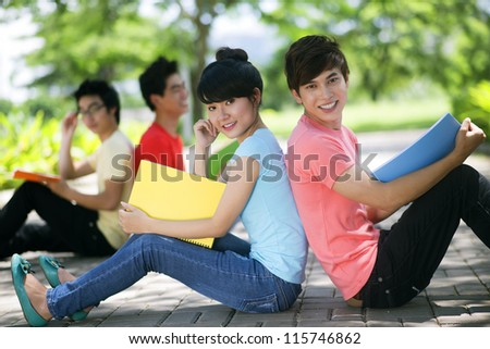 Two student friends sitting on the ground outdoors and smiling - stock photo