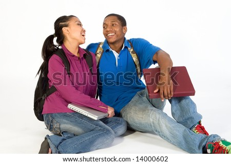 Two Students are sitting on the ground looking at each other. Both wear backpacks and he carries a notebook. Horizontally framed photograph