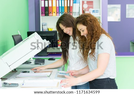 Two students at a copy center taking some copies for their final exams #1171634599