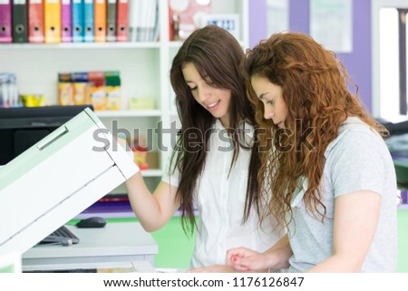 Two students at a copy center taking some copies for their final exams #1176126847