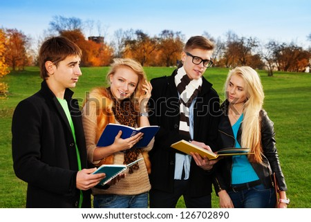 Two students couples in park with blond women happy and smile, holding a book