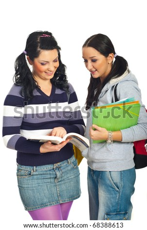 Two students girls reading from a book and having a conversation isolated on white background