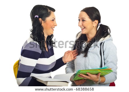 Two students girls standing face to face  having an conversation and laughing together isolated on white background