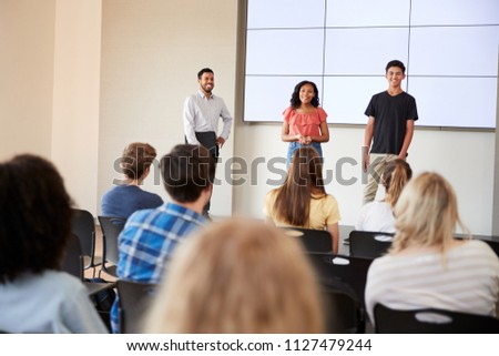 Two Students Giving Presentation To High School Class In Front Of Screen