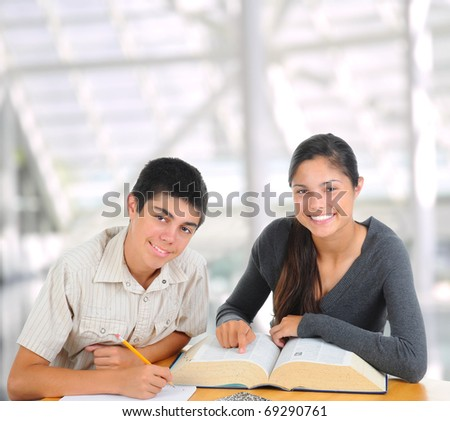 Two students in modern educational facility. Teenage boy and girl with books open on their desk. Square format. Back to school concept.