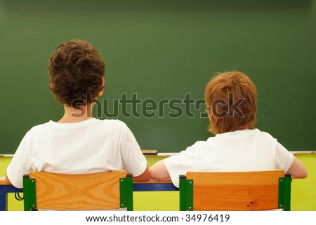 Two students in the classroom with blackboard as background