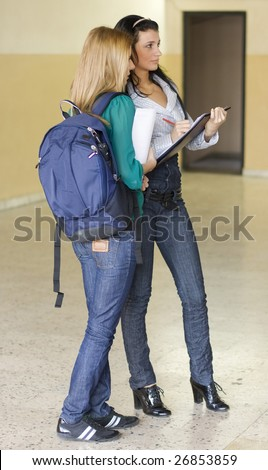 Two students  in the university corridor noting down something