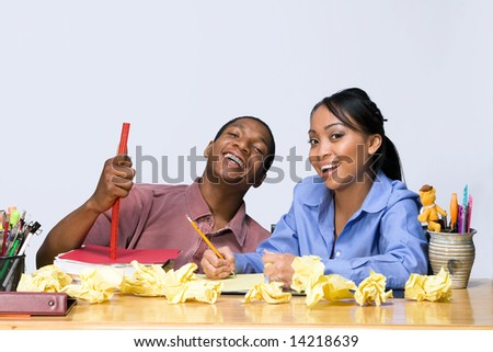 Two students laughing as they sit at a desk. Horizontally framed shot.