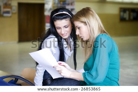 Two students learning together in the university corridor before an exam