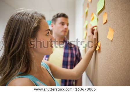 Two students looking at notice board  at college