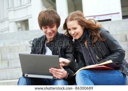 Two students sitting in park on grass with computer notebook