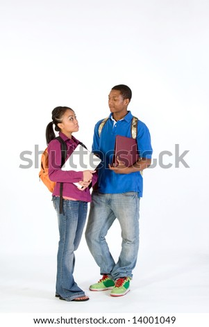 Two students stand and look at  each other with worried expressions on their faces. They wear backpacks and he carries a notebook. Vertically framed photograph.