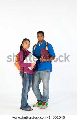 Two students stand and look at  the camera with serious expressions on their faces. They wear backpacks and he carries a notebook. Vertically framed photograph.