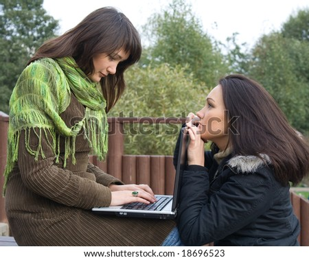 Two students studying outdoor with laptop before exam