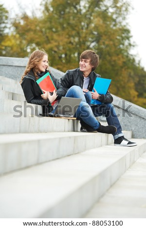 Two students studying with computer notebook and workbooks outdoors