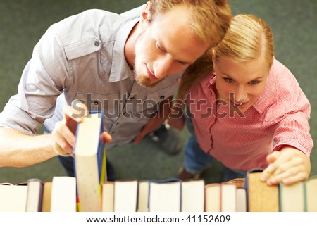 Two students taking books from a shelf
