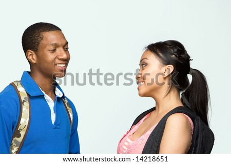 Two students wearing backpacks look at each other and laugh. Horizontally framed photograph