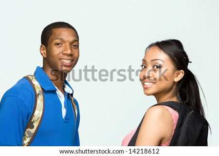 Two students wearing backpacks look at the camera and smile. Horizontally framed photograph - stock photo