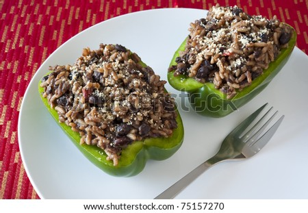 Two stuffed green peppers on a red and gold table cloth