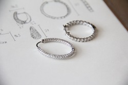 two style of white gold hoop earrings with diamond pave set on white paper and hand sketch drawing with selective focus