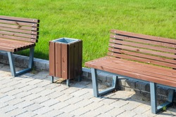 Two stylish benches and a trash can in a summer park along a paved path against a green lawn. Small architectural forms concept