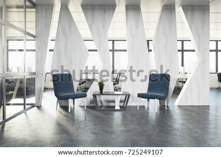 Two stylish blue armchairs are standing near a coffee table in an office waiting area. An open space room is in the background. 3d rendering mock up