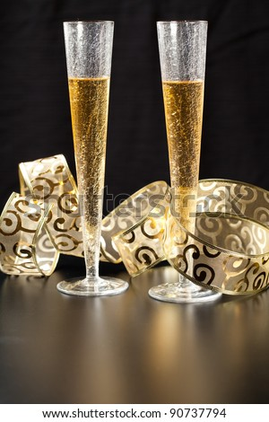 Two stylish glass of champagne with gold festive decorations against black background