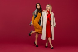 two stylish women in autumn winter fashion dress and coat posing isolated full heigth on red studio background
