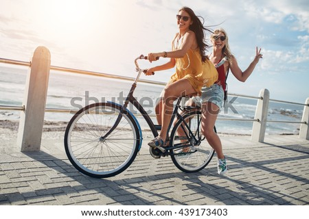 Two stylish young female friends on a bicycle along seaside. Best friends enjoying a day on bike. #439173403