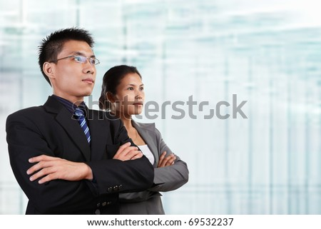 Two successful Asian business people looking at empty space, with blur glass windows as background