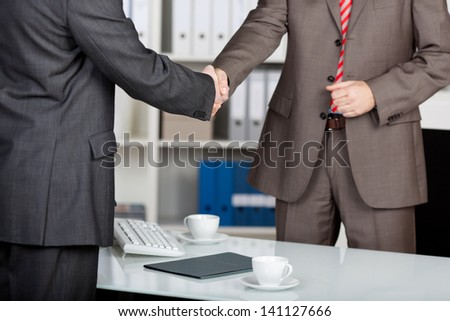 Two successful business partner shaking hands in the office