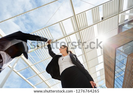 Two successful business people make high five in front of business office