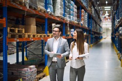 Two successful business people walking through large warehouse center. Manager smiling and looking shelves full with packages and products. Warehouse workers talking about logistics and distribution.