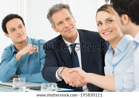 Two Successful Businessmen Shaking Hands In Front Of Their Colleague