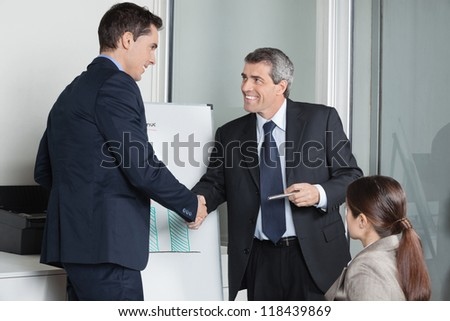 Two successful businesspeople giving handshake in the office