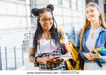 Two successful multiethnic female students with backpaks talking with each other in cheerful way. Cheerful females in university campus park outdoor. Youth Friendship Together Happiness Concept. #1445915756