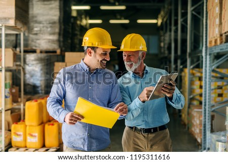 Two successful smiling business man walking through big warehouse with helmets on their heads. Older man is holding digital tablet and shoving younger one some documents. Foto stock ©