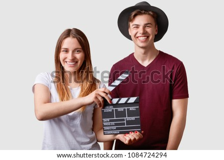 Two successful young female and male famous producers or directors hold film clapper, participate in shooting film, have joyful expressions, pose against white background. Film making concept. #1084724294