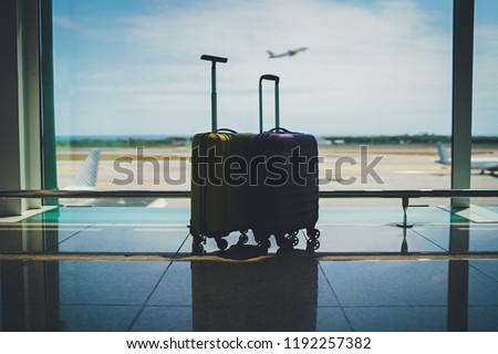 Two suitcases in airport departure lounge, luggage in airport waiting area, vacation or business travel concept, aircraft taking off on the background